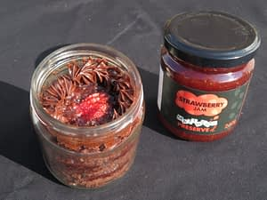 A chocolate cake made in a jar with buttercream icing and Matthew's Preserved Strawberry Jam